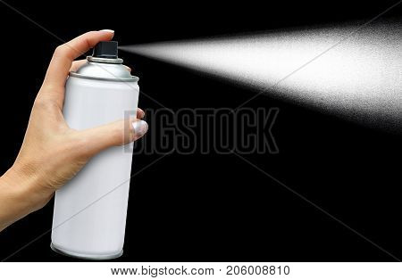 The dispersion jet from an aerosol can in feminine hand on dark background