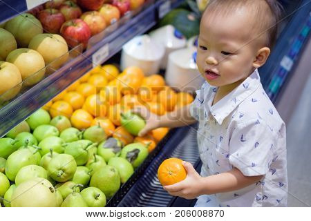 Cute little Asian 18 months / 1 year old toddler baby boy child shopping in a supermarket. Kid standing choosing and holding fruit in grocery store Kid first experience concept - Selective focus