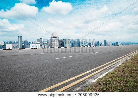 empty asphalt road and modern buildings in nanjing in blue sky