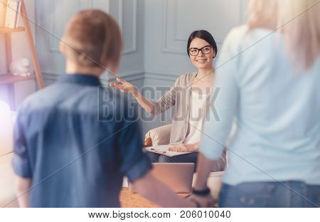 You are welcome. Charming cheerful female school psychologist welcoming teen boy and his mother while getting ready to strart a psychological session