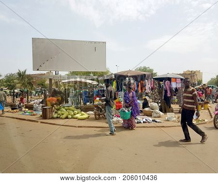 BAMAKO MALI - DEC 19 2016: View from the humanitarian vehicle of a generic urban market shopping street of the Bamako with people selling on the streets diverse object and vegetables