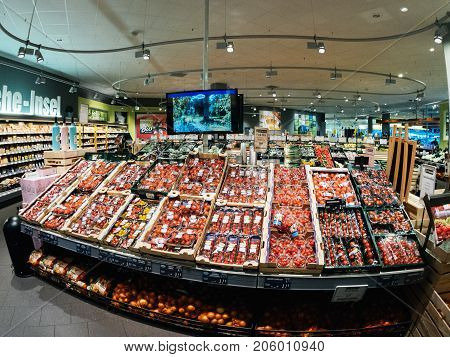 FRANKFURT GERMANY - MAY 3 2017: Large supermarket shelf with diverse types of tomatoes goes on sale for the impatient customers of the German supermarket Edeka