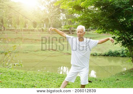 Portrait of healthy white hair Asian senior man practicing wushu at outdoor park in morning.
