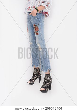 Fashion. Woman legs in embroidered flowers with high heels shoes casual style isolated on white background