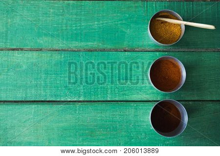 Overhead of cinnamon powder, chili powder and curry powder on wooden table