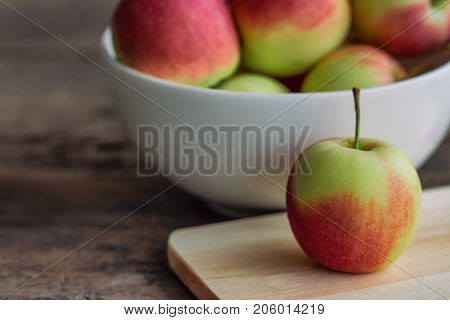 Fuji apple on cutting board put on rustic wood table and stack in white bowl with copy space.Delicious sweet and juicy fuji apple suitable for salad cooking or bakery. Fuji apple has origins in Japan. Prepare apples for cooking or baking.