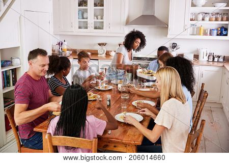 Two Families Enjoying Eating Meal At Home Together