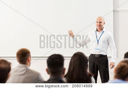 business, education and people concept - smiling businessman or teacher with remote and group of students at conference presentation or lecture