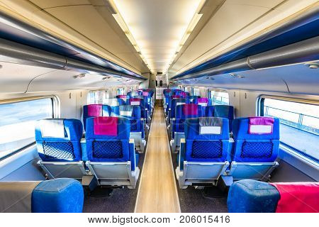 Empty interior of a passenger train. Unoccupied seats in economy or second class. Public transport.
