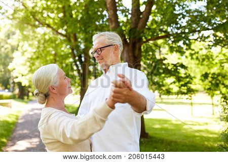 old age, relationship and people concept - happy senior couple dancing waltz at summer city park
