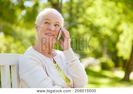 retirement, communication and old people concept - happy senior woman calling on smartphone in summer