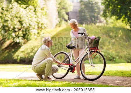 active old age, people and lifestyle concept - happy senior couple with fixie bicycle at summer city park