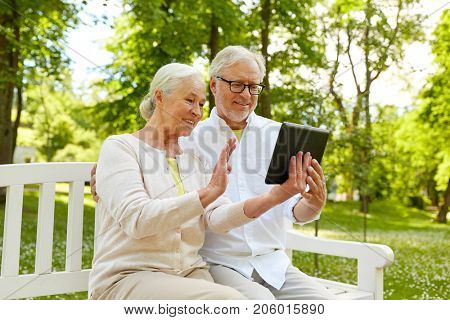 retirement, technology and old people concept - happy senior couple with tablet pc computer at summer park