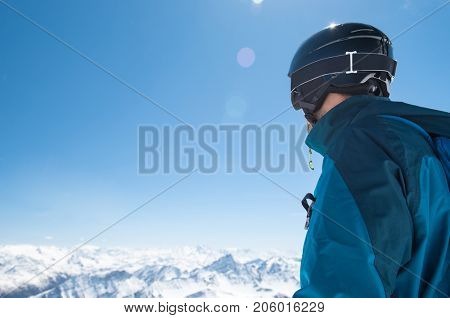Rear view of man in snowy mountain wearing helmet and looking the snowy landscape. Skier man looking at mountains from peak with copy space. Back view of man doing cross country skiing.