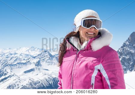 Happy woman with mask for snowboarding looking away with mountains covered by snow in background. Smiling girl skier wearing ski glasses in winter with copy space. Woman during winter vacation.