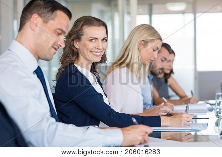 Portrait of beautiful mature businesswoman sitting in a meeting room with her colleagues. Happy business team sitting in a row during conference. Businesspeople taking notes during seminar.