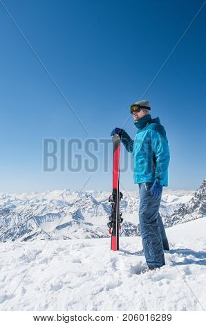 Thinking smiling man doing ski touring in winter mountain. Skier holding a pair of skis and looking at the snowy mountains. Sporty man wearing ski goggles. Winter holiday and ski sport concept.