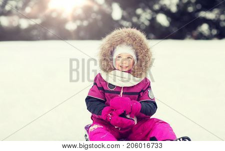 childhood, sledding, fashion, season and people concept - happy little kid on sled outdoors in winter