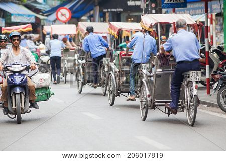 HANOI VIETNAM - AUGUST 2017: Caucasian tourists travelling by cyclo in the Old quarter of Hanoi