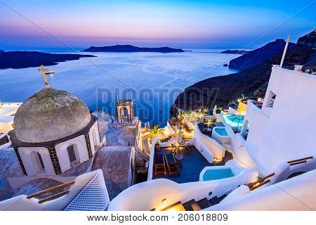 Fira Santorini - Greek Islands landmark with white village cobbled paths greek orthodox blue church and sunset over caldera. Cyclades Greece.