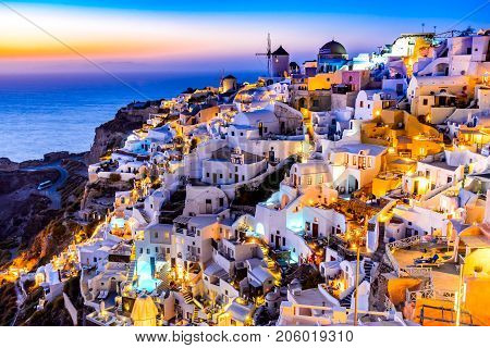 Oia Santorini - Greece. Idyllic attraction of white village with cobbled streets and windmills Greek Islands of Cyclades.