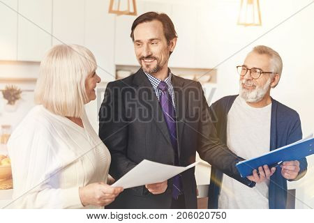 I will provide my assistance. Cheerful professional insurance agent holding papers and talking with aged couple while being involved in work