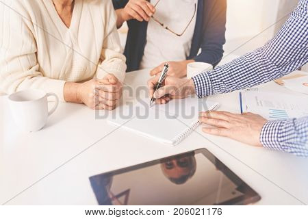 Pros and cons. Professional pleasant real estate agent sitting on the table while meeting in the kitchen with aged couple