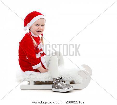 joyful little girl in santa suit sitting on a sleigh