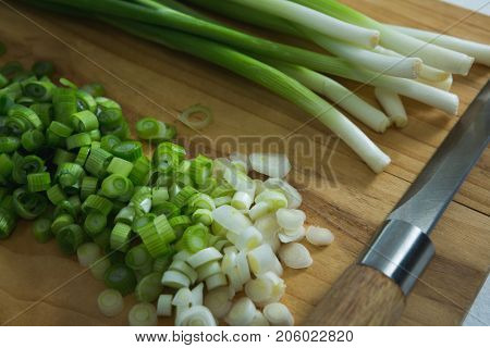 Close-up of chopped scallions with knife on chopping board