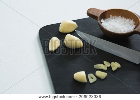 Chopped garlic with bowl of sea salt and knife on chopping board