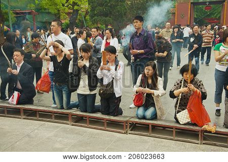 BEIJING, CHINA - MAY 01, 2009: Unidentified worshippers hold incense sticks and pray at Yonghegong Lama Temple in Beijing, China.