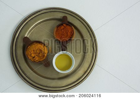 Spices powder with oil in bowl on tray