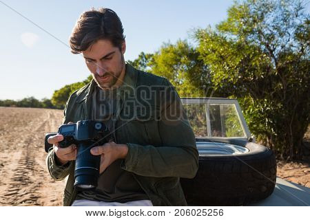 Young man looking at camera while sitting on vehicle hood at field