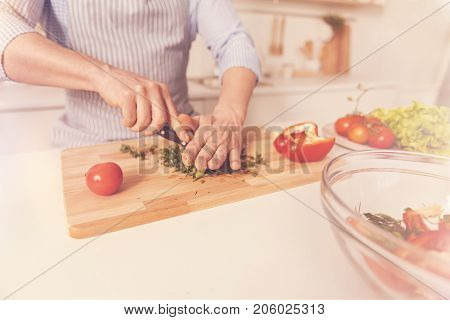 Healthy food. Close up of a knife in hads of pleasant man cutting vegetables while cooking salad and standing in the kitchen