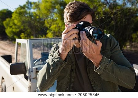 Man photographing from camera by parked vehicle on field