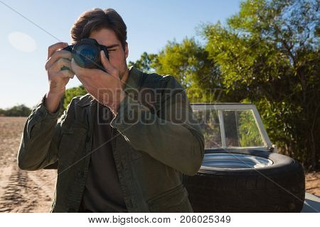 Young man photographing by parked vehicle on field
