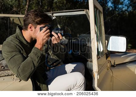 Man photographing while sitting in off road vehicle