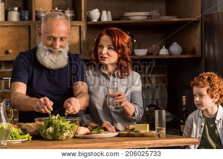 portrait of grandparents cooking salad and little boy sitting at table