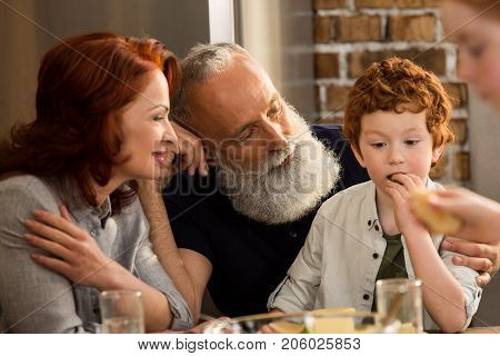 grandparents looking at little boy eating snack