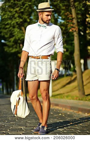 Handsome hipster model man in stylish summer clothes posing on street background in hat with bag