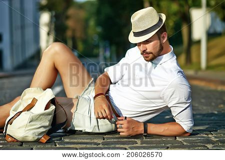 Handsome hipster model man in stylish summer clothes sitting on street background in hat with bag