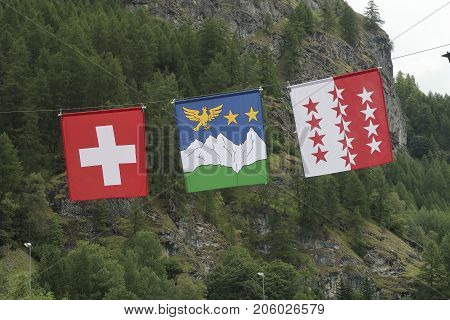 Three flags of Switzerland Wallis and Val d'Hérens next to each other in front of a mountain and trees