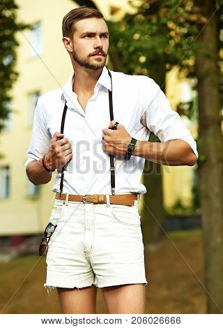 Handsome hipster model man in stylish summer clothes posing on street background