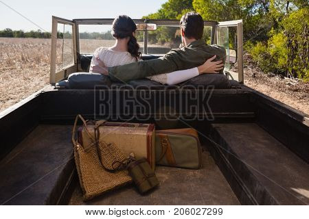 Rear view of couple with arms around sitting in off road vehicle on landscape