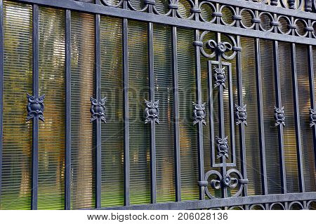 a fragment of a gray fence with forged bars and a beautiful pattern