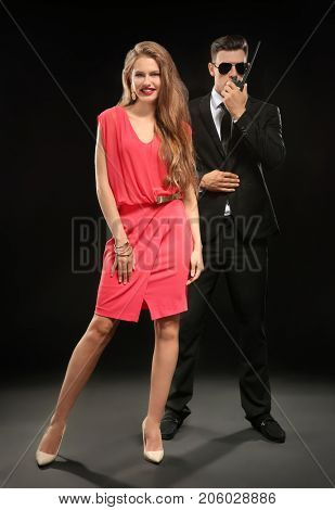 Famous celebrity with bodyguard on dark background