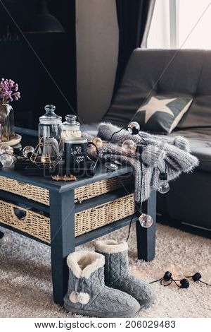 Still life details of living room interior. Cup of coffee on rustic wooden tray, candle and warm woolen sweater on table, decorated with led lights. Autumn weekend concept. Fall home decoration.
