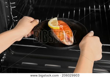 Woman putting portioned frying pan with salmon steak into oven