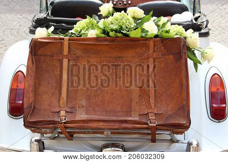wedding day old white cabriolet with a leather suitcase on its back filled with white roses