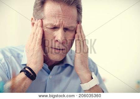 Awful migraine. Cheerless moody nice man holding his temples and closing eyes while having migraine